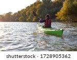 Woman Rowing On Green Kayak On...