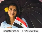 Woman With Umbrella Holds Flag...
