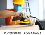 Close-up of male worker holding sander machine and working with wood. Handyman wearing protective yellow helmet and gloves. Polishing table at construction site. Renovation concept