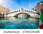 Beautiful view from the Canal Grande to the famous Rialto Bridge in Venice, Italy, without people and clear, emerald water - stock photo