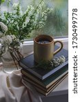 Small photo of Branches of blooming Spiraea in a Glass vase and a ceramic cup with coffee on a stack of books by the window. Close up. Morning still life. Rainy day