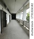 Small photo of a long balcony in a city building with white walls and black doors. The opening is well lit with natural light but the tunnel leads to darkness at its end. It gives a mundane colorless look of city.
