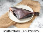 Small photo of Dory's raw fish in a white plate on the light gray kitchen table. Dory fish close up