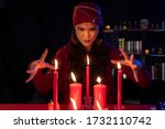 Small photo of Beautiful Gypsy fortune teller woman casting a magical spell over candle while predicting the future. Divine magic, Forecast esoteric astrology superstition, magical power, alchemy, Black magic.