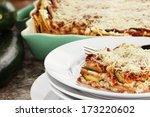 Stock photo a serving of zucchini lasagna with fresh zucchini and casserole dish in background 173220602