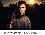 Hunting Gear - Hunting Supplies and Equipment. Hunter with shotgun gun on hunt. Illegal Hunting Poacher in the Forest. Close up Portrait of hamdsome Hunter - stock photo