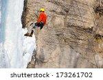 man climbing frozen waterfall | Shutterstock . vector #173261702