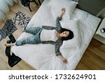 top view of taiwanese woman lying in a sprawl on bed with her clothes scattered on floor. asian young girl hanging out with friend until dawn goes to bed straight without taking bath.