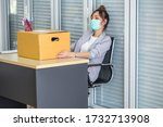 Small photo of Asian women wear medical masks, store belongings after being laid off due to covid 19 disease Outbreak caused bankruptcy.Lay off and the economy concept.