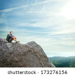 young man sitting on a rock | Shutterstock . vector #173276156
