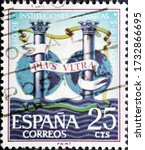 Small photo of MADRID, SPAIN - MARCH 18, 2020. Vintage stamp printed in Spain shows the Pillars of Hercules bearing the motto Plus ultra, the national motto of Spain, following the discovery of the New World