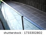 Small photo of Tempered laminated glass railing balustrade panels frame less ,safety glass for modern architectural buildings. Concept image for exterior path railing and landscape design.