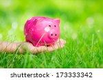 Piggybank In Hand Over Green...