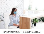 Small photo of Receptionist wearing medical mask in office. Protection employees on workplace. Young woman working at reception in hotel. Disease prevention during quarantine, staff safety.