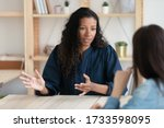 Small photo of Close up confident african american businesswoman explaining new responsibilities to female applicant. Attractive young diverse woman hr manager talking and introduction company to job seeker.