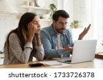 Small photo of Mad millennial couple frustrated with slow Internet connection paying bills online in kitchen, confused young husband and wife angry with unexpected error mistake using internet banking on computer