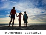 Silhouettes of mother and kids at beach during sunset - stock photo