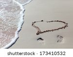 Heart drawn on beach sand and sea wave  - stock photo