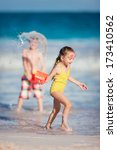 Two kids playing at tropical beach during summer vacation - stock photo