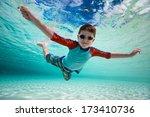 Cute little boy swimming underwater in tropical sea - stock photo