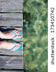 Woman legs wearing flip flops at wooden jetty by the sea - stock photo