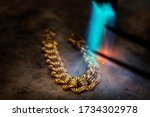 Small photo of Goldsmith makes gold necklace, use high fire blow soften the gold for easy formatting,which tradition method.