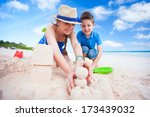 Young mother and her son at tropical beach making sandcastle - stock photo