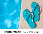 Turquoise flip flops by a swimming pool  - stock photo