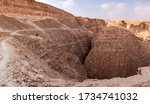 Panoramic desert landscape with an impressive view on a narrow gorge of wadi Barak in Arava desert, Israel.  Hikers on a hiking trail above a gorge of wadi Barak.