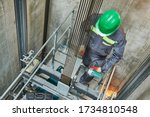 Small photo of lift machinist repairing elevator in lift shaft