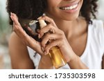 Small photo of Split Ends Repair Treatment. Smiling African Woman Applying Essential Oil Spray On Her Curly Brown Hair At Home, Cropped Image, Closeup