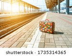 A Retro Suitcase Stands On An...
