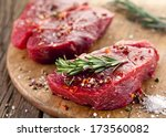 raw beef steak on a dark wooden ... | Shutterstock . vector #173560082