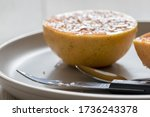 Small photo of Grapefruit knife and spoon in front of grilled grapefruit (focus on knife). Serrated curved grapefruit knife on a grey plate with serrated spoon. Selective focus.