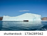 Rubber boat floating in front of big iceberg. Eqip Sermia, Greenland.