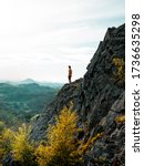 Small photo of Man hiking on top of a rocky mountain peak. Steep cliff, rocky part of path with view into distance. Scenic landscape of Lunation Mountains, Czech Republic