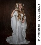 Small photo of Art photograph of a languid girl in an elven white dress with a barn owl on her shoulder