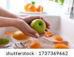 Hands Of Woman Washing Apple...