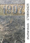 """""""1907"""" chiselled out of stone and polished. Partly covered with sand"""