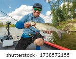Small photo of Success fishing. Fisherman with asp aspius fish on boat at wild river