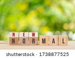 """Small photo of The text on wooden cube """"NEW NORMAL"""". The new normal after COVID-19 pandemic concept. a previously unfamiliar situation that has become standard."""