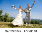 Groom and the bride jumping against backdrop a sky and trees. In all growth. - stock photo