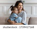 Smiling Mother Hugging Little...