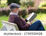 Caucasian old man reads a book...