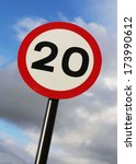 Small photo of Twenty miles per hour speed limit sign against a partly cloudy sky.