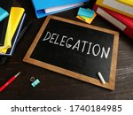 Small photo of Delegation written in chalk on a blackboard. Delegating concept.