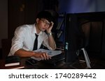 Small photo of Stressed Young asian business man working late night alone in office late his eyes are gonna closing at table and looking headache sleepy, overtime overload working concept.