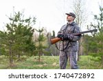 A hunter with a shotgun in his hands stands in a forest clearing in the evening and waits for the appearance of wildfowl