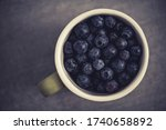Fresh Forest Fruits. Cup Full of Blueberries Top View. Highbush Blueberry Fruit. Healthy Eating Theme. - stock photo