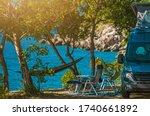 Scenic Outdoor Camping Spot. Motorhome, Garden Chairs and Hammock Between Trees. Sea Shore Scenery. Vacation Time in Camper Van. - stock photo